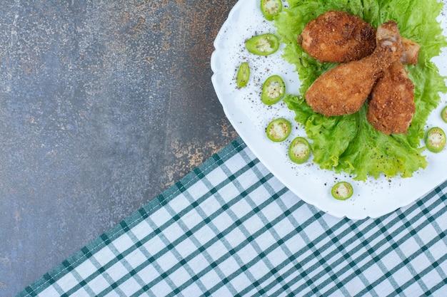 후추와 하얀 접시에 양상추와 치킨 나지만. 고품질 사진