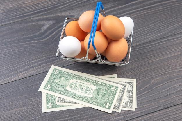 木製のテーブルに鶏卵とドル。食品の販売