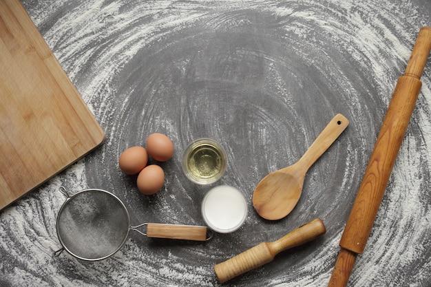 Куриное яйцо, мука, оливковое масло, молоко, кухонный инструмент на сером фоне стола.