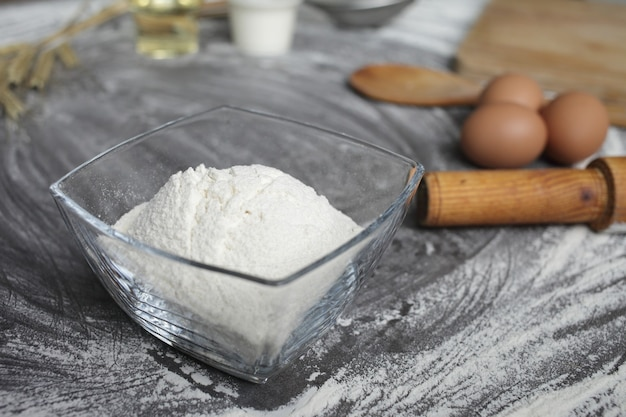 Chicken egg, flour, olive oil, milk, wheat ears, kitchen tool on gray table background.