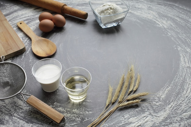 닭고기 달걀, 밀가루, 올리브 오일, 우유, 밀 귀, 회색 테이블 배경에 주방 도구.