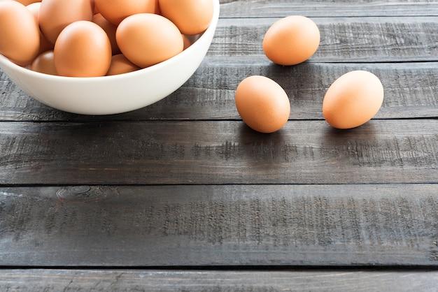 白いボウルの鶏の卵と黒い色の木製のテーブルの上の3つの鶏の卵