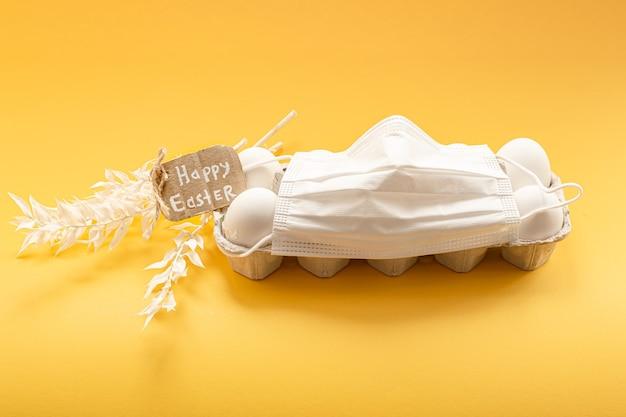 닭고기 달걀 트레이 및 보호 의료 마스크. 코로나 바이러스 전염병 동안 행복 한 부활절 개념입니다.