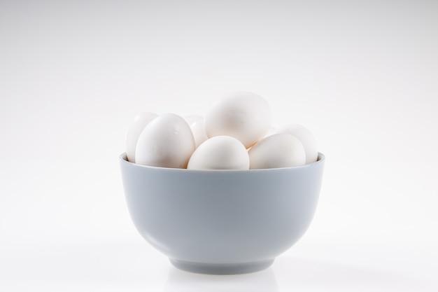 チキンエッグ、白いテクスチャ背景のセラミックボウルに置かれた白い卵。