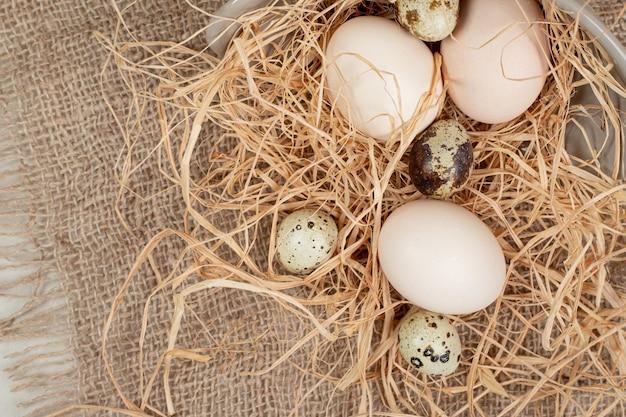 Куриное яйцо с перепелиными яйцами и сеном на мешковине.