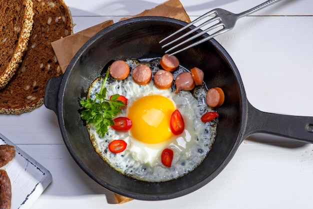 Chicken egg with sausage slices in a round black cast-iron frying pan a