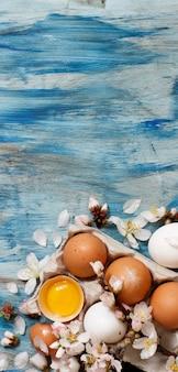 青い木製の背景に鶏卵とアーモンドの花