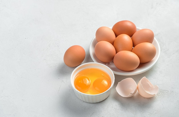 회색 배경에 닭고기 달걀과 원시 노른자. 측면 보기, 복사 공간입니다.
