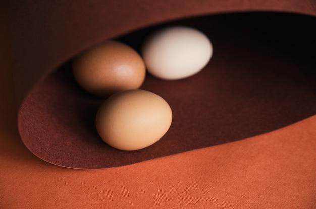 茶色の紙の上に鶏の卵を一列に並べます。紙はらせん状または楕円形に丸められます。休日のイースターエッグ。