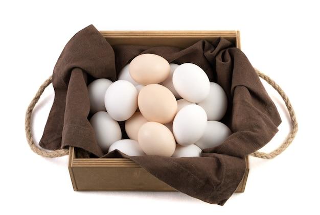 Куриные яйца бело-коричневого цвета в красивой деревянной упаковке с коричневой льняной салфеткой.