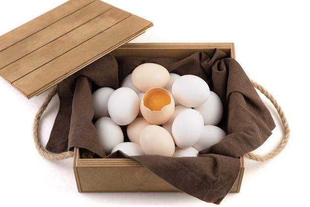 Куриные яйца бело-коричневые с разбитым яйцом в центре, в котором виден свежий желток.