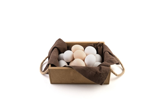 Chicken eggs are white and brown in a beautiful wooden package with a brown linen napkin.
