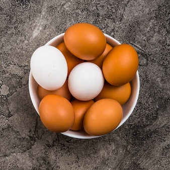 Chicken eggs in bowl on grey table