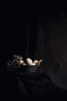 Chicken eggs in bowl near plant