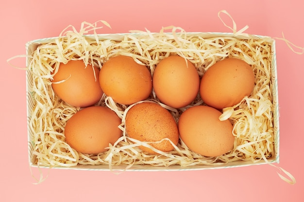 Chicken eggs in a box on a pink pastel background, copies of space, flatlay