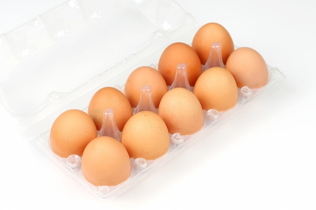 Chicken eggs in a box on white