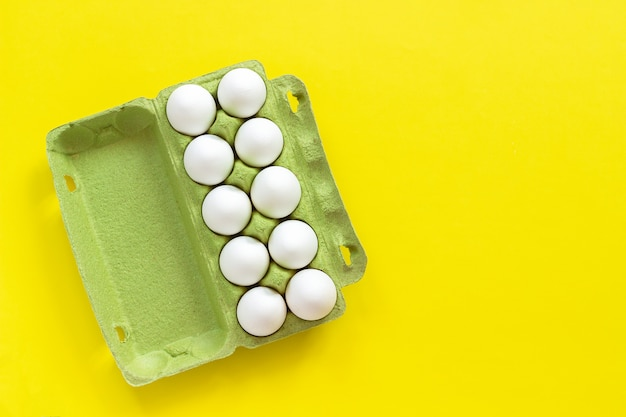 Chicken eggs in cardboard box on yellow paper background