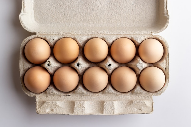 Chicken eggs in a cardboard tray. top view