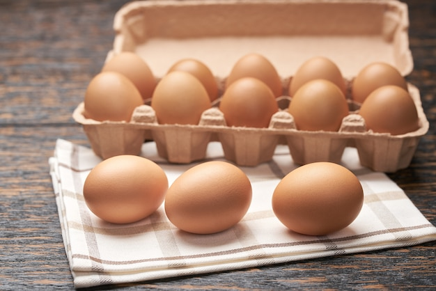 Chicken eggs in carton box on a kitchen table