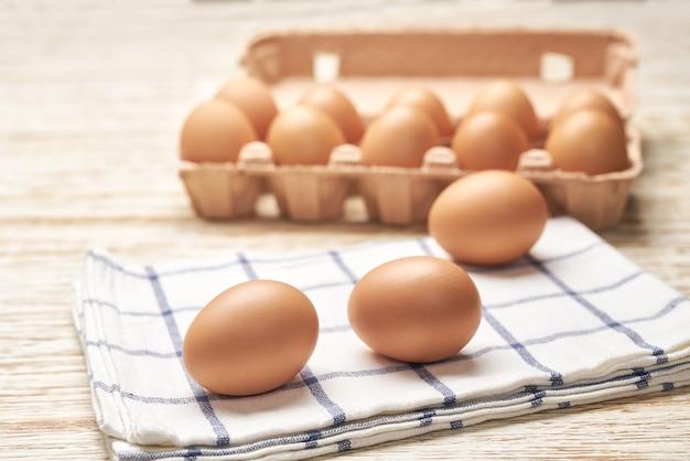Chicken eggs in carton box on a white wooden table, selective focus.