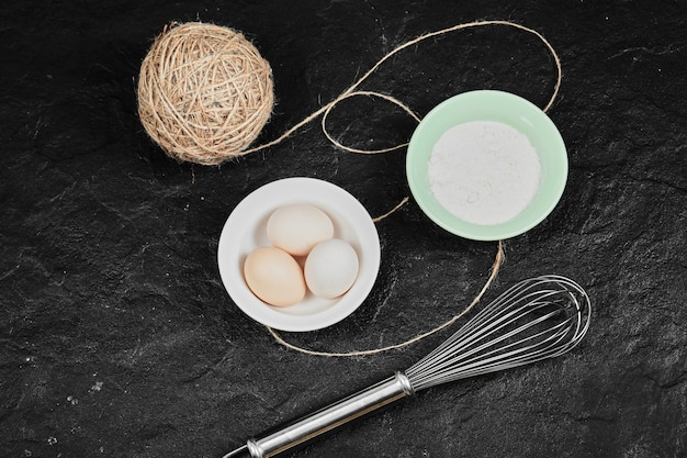 Chicken eggs on ceramic plate and a bowl of flour on dark table with whisker.