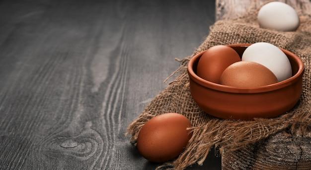 黄麻布のベッドの上の粘土のボウルの鶏卵のクローズアップ。テキストのコピースペースと黒い木製の背景