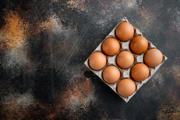 Chicken eggs in an egg box tray set, on old dark rustic