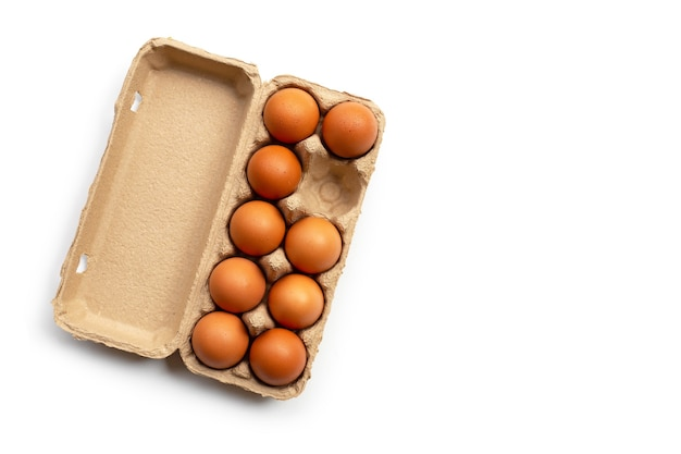 Chicken eggs in egg box on a white surface