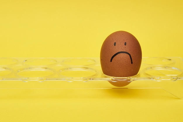 Chicken eggs in an egg holder. half an egg, egg yolk, shell. emotion and facial expression painted on eggs.