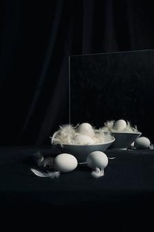Il pollo eggs fra le piume in ciotola vicino allo specchio