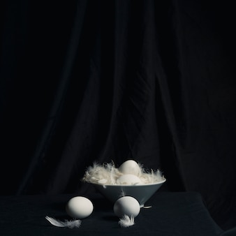 Chicken eggs between feathers in bowl