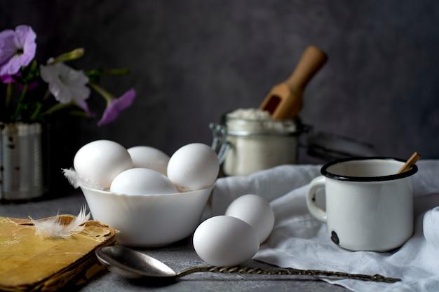 Куриные яйца, мука, молоко и старая книга рецептов на кухонном столе
