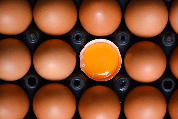 Куриные яйца из фермерских продуктов, натуральные в коробке, концепция здорового питания / свежий разбитый яичный желток