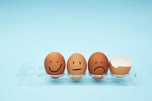 鶏の卵。卵の完全なトレイ。半分の卵、卵黄、殻。卵に描かれた感情と表情。