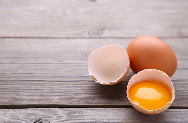 Chicken eggs and half with yolk on a grey background.