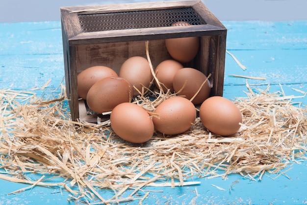테이블에 짚이 있는 상자에 있는 닭고기 달걀