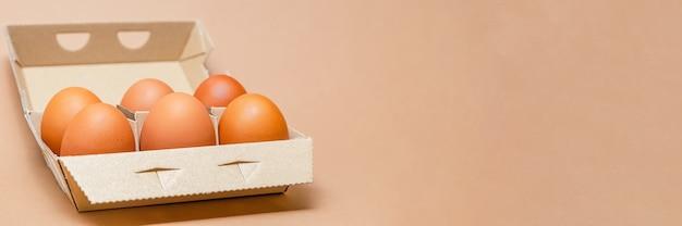 Куриные яйца в картонной коробке, место для текста, широкий формат. коричневый фон.