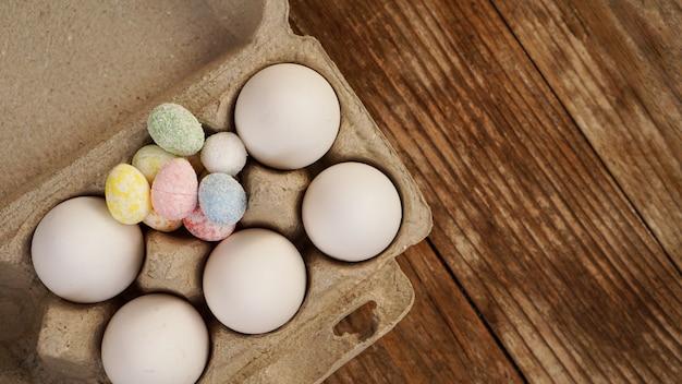 Куриные яйца в картонном подносе и пасхальный декор на деревянном фоне., сельский стиль