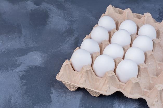Куриные яйца в картонном лотке.