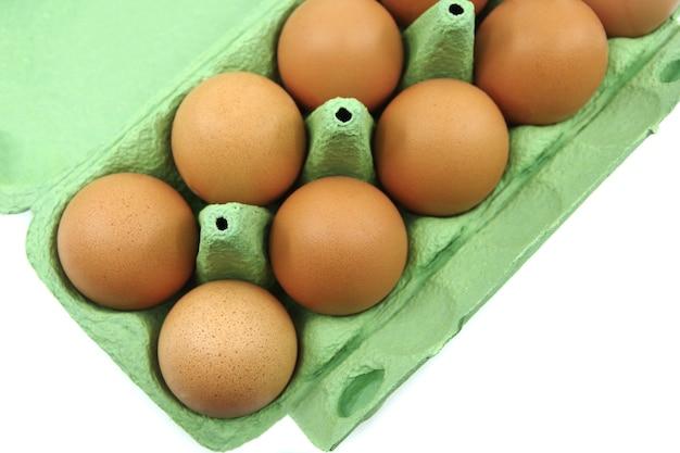 녹색 계란 용기에 닭고기 달걀. 계란 흰 배경에 고립 된 컨테이너입니다.