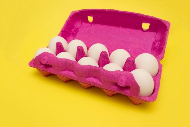 노란색 바탕에 계란에 대 한 분홍색 상자에 닭고기 달걀. 부활절 전에 계란을 구입합니다.