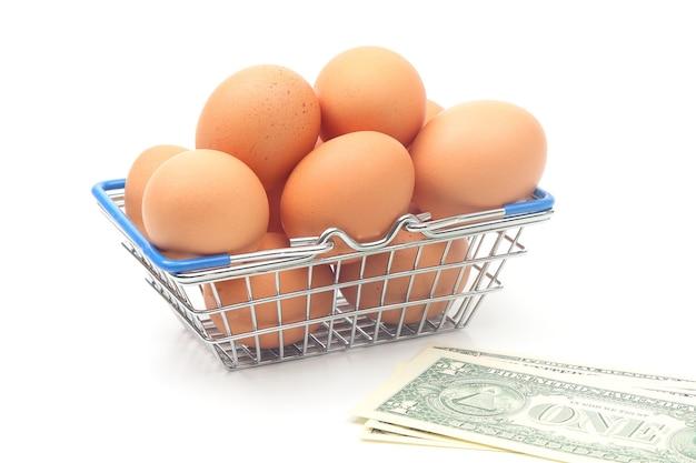 スーパーマーケットの食料品バスケットの鶏卵と白い背景のドル。食品の販売・事業