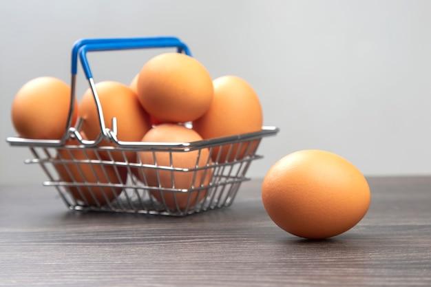 나무 배경에 슈퍼마켓 식료품 바구니에 닭고기 달걀.