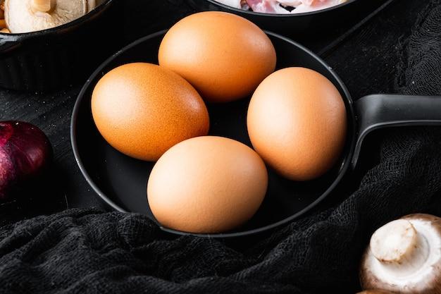 검은 나무 테이블 배경에 계란 상자 트레이 세트에 닭고기 달걀