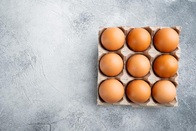 회색 배경에 설정된 달걀 상자 트레이에 있는 닭고기 달걀, 위쪽 보기 평면 레이아웃, 텍스트 복사 공간이 있는 공간