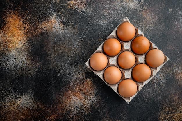 오래된 어두운 시골풍의 달걀 상자 트레이 세트에 있는 닭고기 달걀