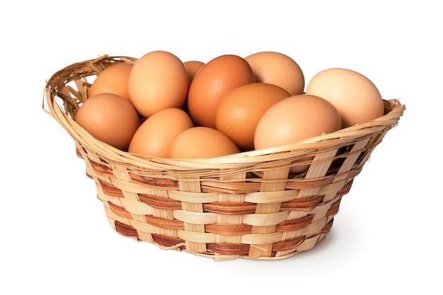 Куриные яйца в корзине изолированного на белой поверхности крупным планом