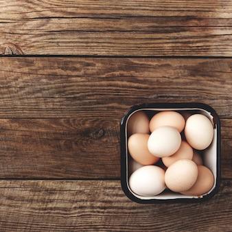 Куриные яйца в корзине на деревянных фоне органических домашних хозяйств