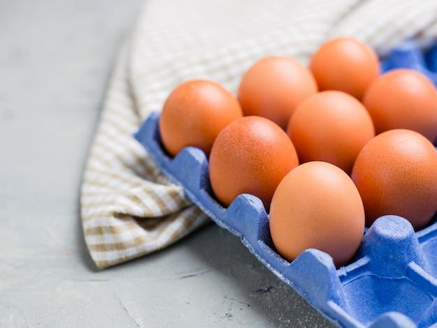 灰色の石のテーブルの上の青いカートンボックスの鶏卵