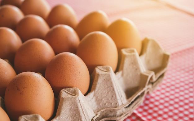 Куриные яйца в картонной коробке на классической розовой скатерти с выборочным фокусом